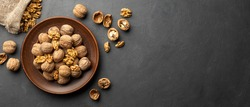 Nuts. Walnut kernels and whole walnuts on dark stone table. Black background. Top view, flat lay with copy space.