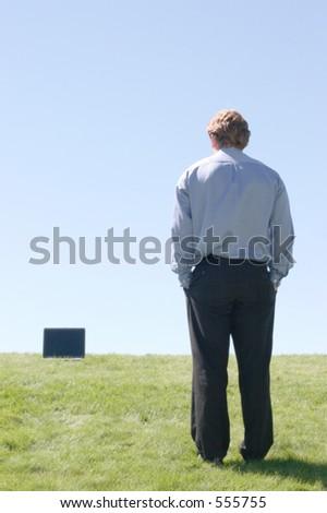 O homem de negócios, com mãos em uns bolsos, anda uphill aseu laptop. Senta-se na grama verde de encontro a um céu azul - stock photo