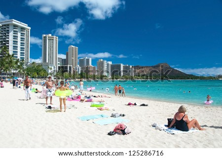 OAHU, HI - SEPTEMBER 27, 2011 - Tourist sunbathing and surfing on Waikiki beach September 27, 2011 in Oahu.  Waikiki beach is beachfront neighborhood of Honolulu, best known for white sand and surfing