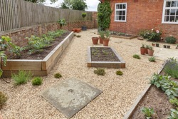 Oak sleeper raised beds in a courtyard garden design with hard landscpaing, gravel and terracotta pots