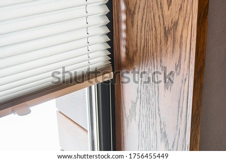Oak veneer window slopes. Wooden slopes on the window. Window with pleated shades. Close-up ストックフォト ©