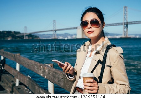 Oakland Bay Bridge San Francisco California has one of the longest spans in the United States. young girl traveler using cellphone searching online guide book relying against handrail drinking coffee