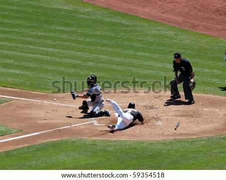 OAKLAND, CA - AUGUST 18: Blue Jays vs. Athletics: Cliff Pennington slides head first into home as Blue Jays catcher waits for incoming ball.  August 18 2010 at Coliseum in Oakland California.
