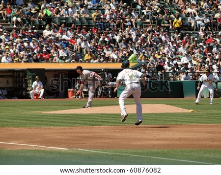 OAKLAND, CA - SEPTEMBER 12: Red Sox vs. A's: Mark Ellis takes lead as Josh Beckett throws pitch.  September 12 2010 Coliseum Oakland California - stock photo