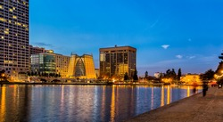 Oakland, California. Evening view across Lake Merritt with reflections of buildings and lights on the water. The