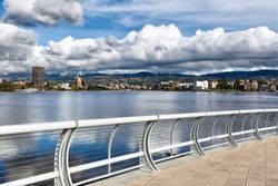 Oakland California view across Lake Merritt of the north shore and the Oakland Piedmont hills, on a day with dramatic storm clouds reflected in the water. Viewed from the new south shore bridge area.