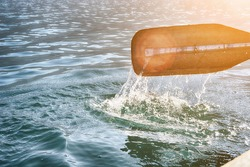 Oar of boat touching water and causing splash and ripples in the water.