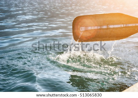 Oar of boat touching water and causing splash and ripples in the water. #513065830