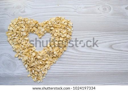 oat flakes are laid out in the form of heart on a simple wooden background #1024197334