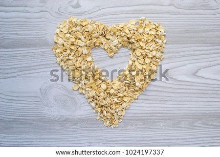oat flakes are laid out in the form of heart on a simple wooden background #1024197337