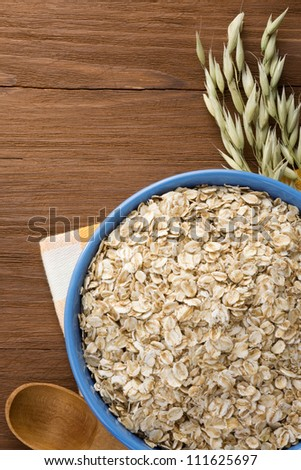 oat flakes in bowl on wooden background