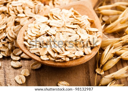 Oat flakes in spoon on wooden table