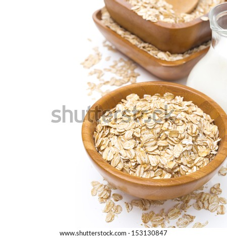 Oat flakes in wooden bowl and a jug of milk, isolated on white