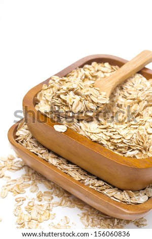 Oat flakes in wooden bowls, isolated on white background