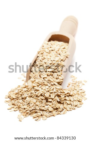 Oat flakes in wooden scoop isolated on white background