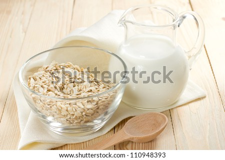 Oat flakes on a glass bowl and jug of milk