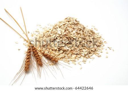 Oat flakes pile and golden ears on white background - stock photo