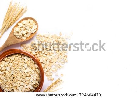 Oat flakes, uncooked oats in bowl with wooden spoon and wheat ears on white background. Concept of healthy eating, vegan food, healthy food, breakfast. #724604470