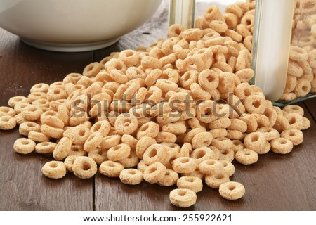 Oat rings cereal spilling out of a glass canister