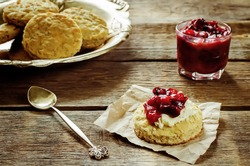 oat scones with cream cheese and caramelized plums on a dark wood background. tinting. selective focus on plums