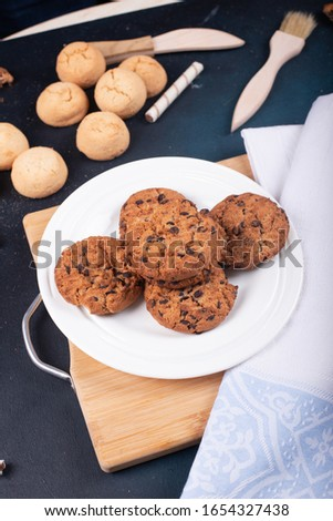 Oatmeal and butter cookies with chocolate chips on a wooden board