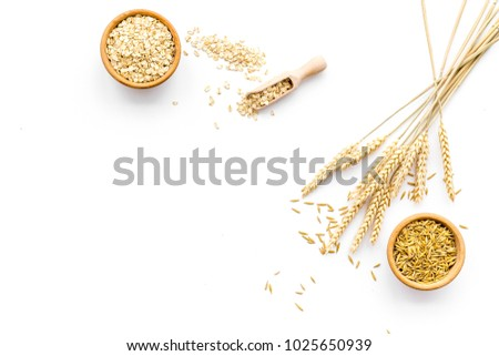Oatmeal and oat in bowls near sprigs of wheat on white background top view copy space #1025650939
