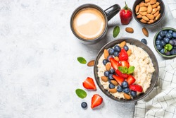 Oatmeal cereal porridge with fresh berries and nuts in black bowl. Healthy breakfast. Top view with copy space.