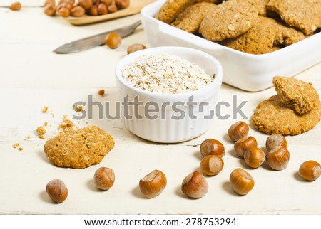 oatmeal cookie chips with hazelnuts on old white wood background #278753294