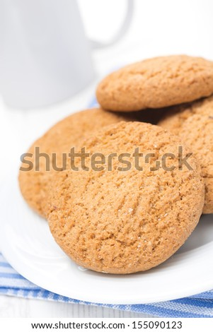 oatmeal cookies on a plate and cup of milk, close-up, vertical