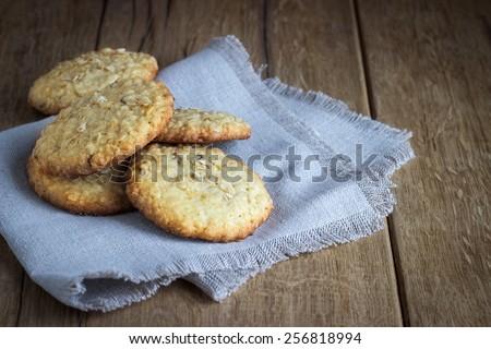 oatmeal cookies on white linen napkin on wooden table. Chocolate chip cookies shot on coffee colored cloth, closeup.