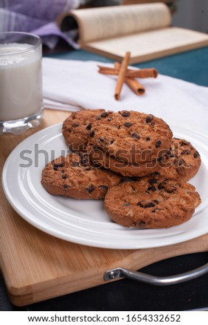 Oatmeal cookies with chocolate chips and a glass of milk on a wooden board