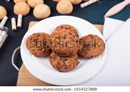 Oatmeal cookies with chocolate chips on a wooden board