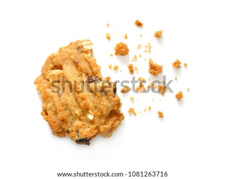 Oatmeal cookies with raisins and cashew nuts with crumbs isolated on white background