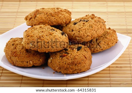 Oatmeal cookies with raisins laying on the white plate. Closeup.