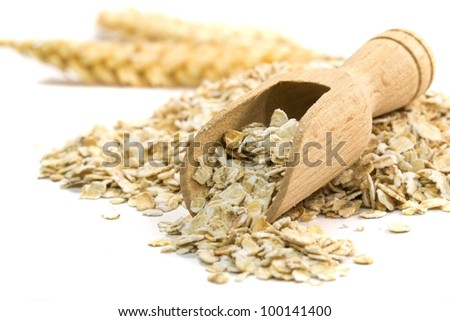 Oatmeal flakes with wooden scoop on white background - stock photo
