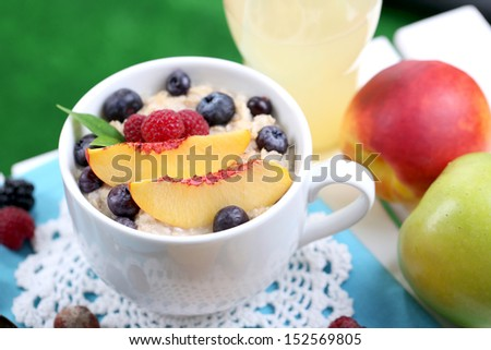 Oatmeal in cup with berries on napkin on table on grass background