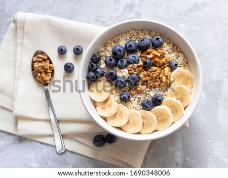 Oatmeal. Porridge with bananas, blueberries and walnut for healthy breakfast or lunch. Natural ingredients. Flat lay design on linen napkin and cement background