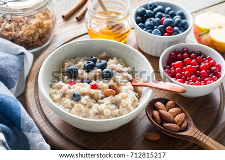 Oatmeal porridge with blueberries, almonds, cinnamon, honey, linseed and red currants in bowl. Super food for healthy nutritious breakfast #712815217
