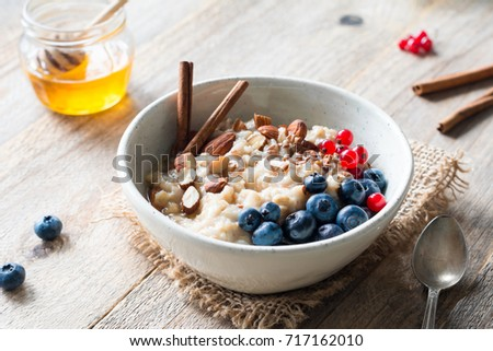 Oatmeal porridge with blueberries, almonds, cinnamon, honey, linseeds and red currants in bowl. Super food for healthy nutritious breakfast #717162010