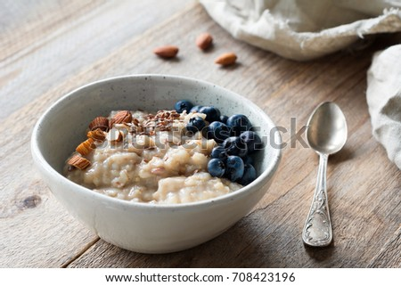 Oatmeal porridge with blueberries, almonds, linseed in bowl on wooden table. Super food for healthy nutritious breakfast #708423196