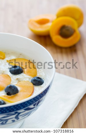 oatmeal porridge with fresh berries and apricots for breakfast on wooden table