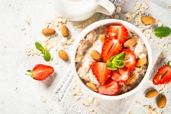 Oatmeal porridge with fresh strawberry and nuts on white background. Healthy breakfast. Top view with copy space.