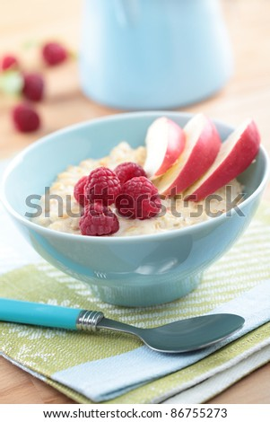 Oatmeal porridge with raspberry and apple in a bowl