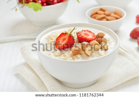 Oatmeal porridge with strawberry slices and nuts in bowl on white table