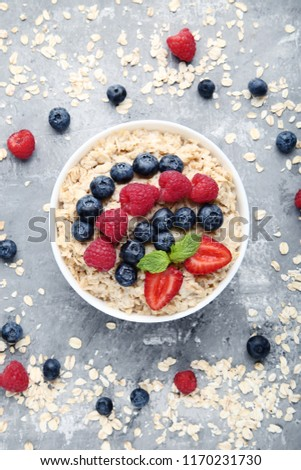 Oatmeal with berries in bowl on grey wooden table