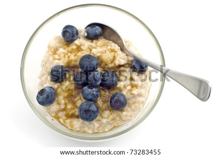 Oatmeal with blueberries in glass bowl isolated on white background