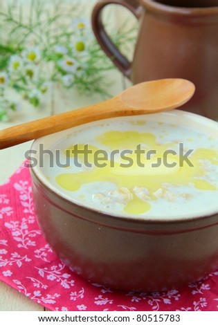 oatmeal with butter in a bowl on a wooden table - stock photo