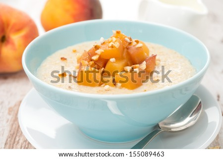oatmeal with caramelized peaches in a bowl and jug of yogurt for breakfast, close-up, horizontal