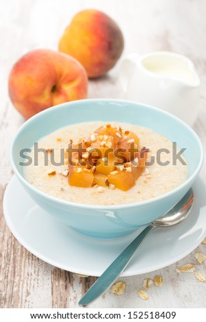oatmeal with caramelized peaches in a bowl and yogurt for breakfast on the table, vertical