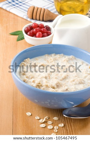 oatmeal with milk and honey on wood background